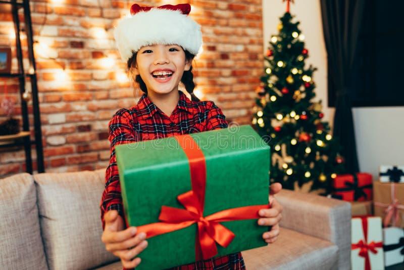 Słodka boże narodzenie dziewczyna pokazuje prezenta pudełko obraz royalty free
