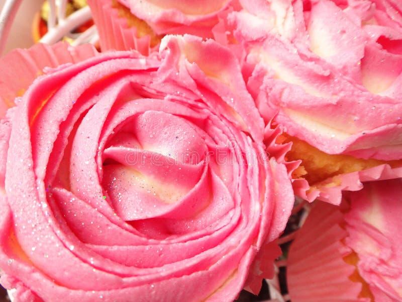 Słodka bułeczka lub babeczki z wzrastali lub kwiat kształtujący różowy masła mrożenie, wyśmienicie deser dla walentynki lub wesel obrazy royalty free