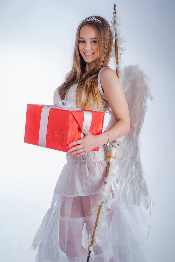 Słodka dziewczyna jest ubranym anioła bielu piórka i sukni kostiumowych skrzydła Walentynki prezenta karta - Wakacyjny nastoletni zdjęcie stock