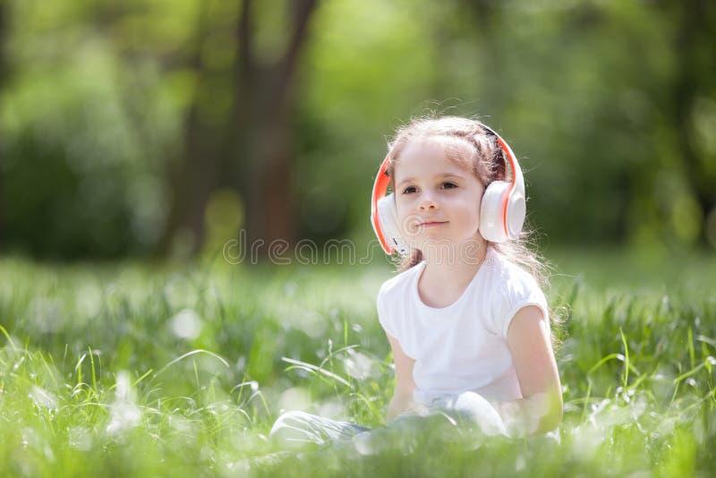 Słodka dziewczynka słucha muzyki w parku Rodzinny styl życia na zewnątrz Szczęśliwego małego dzieciaka w słuchawkach siedzącego n obraz royalty free