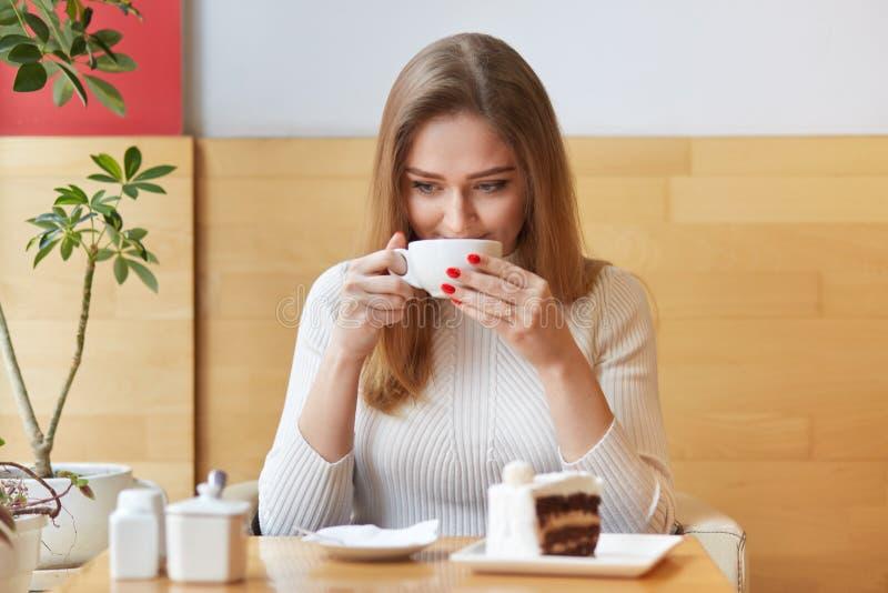 Słodka i szczera kobieta wydaje jej czas w lokalnej kawiarni, wp8lywy odpoczywa podczas lunchu, wp8lywy gorący napój w białej fil obrazy royalty free