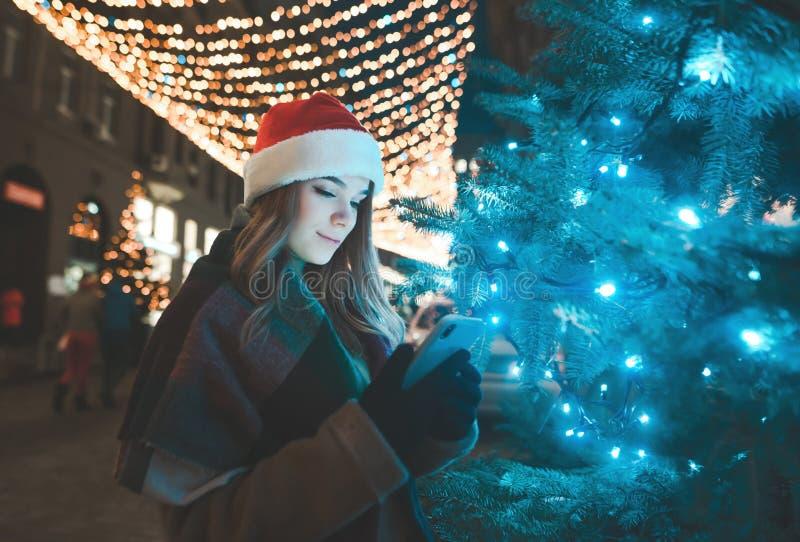 Słodka kobieta w kapeluszu Bożenarodzeniowych stojakach na drzewie na ulicie dekorującej na wakacje i używa smartphone fotografia stock