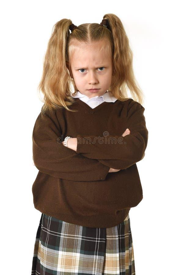 Słodka młoda uczennica w pigtails i mundurka szkolnego przyglądającym gniewnym spęczeniu udaremniającym i nieszczęśliwym fotografia royalty free