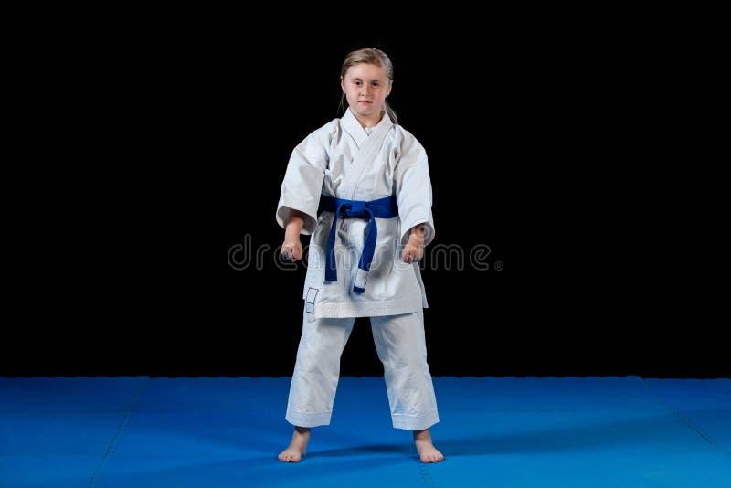 Słodka mała dziewczynka w sztukach samoobrony ćwiczy jak karate dzieciak samotnie odizolowywający na czarnym tle obrazy stock