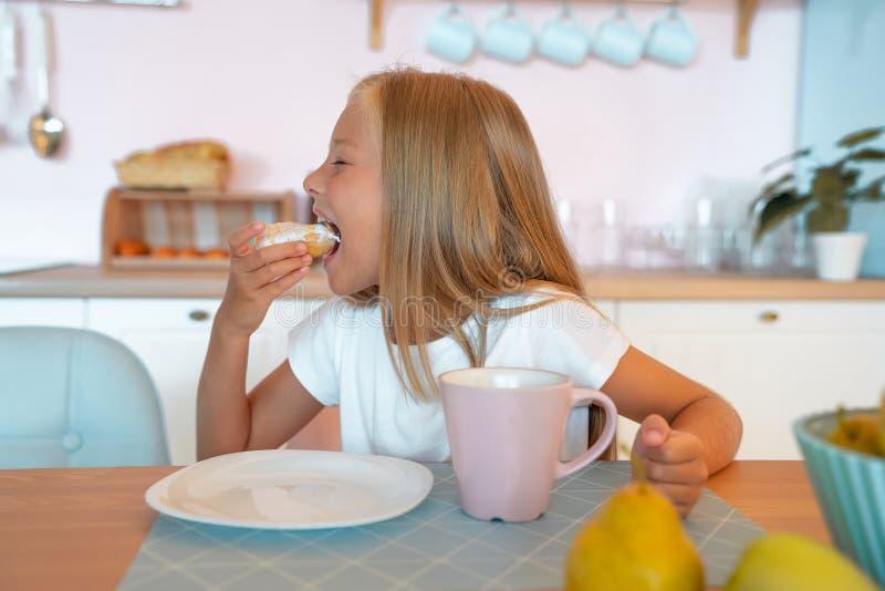 Słodka mała dziewczynka zjem śniadanie w domu, bawiąc się pączkiem z herbatą pyszna żywność obraz royalty free