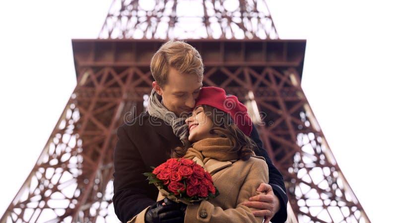 Słodka para ściska tenderly na romantycznej dacie, ładna dziewczyna z róża bukietem zdjęcia royalty free