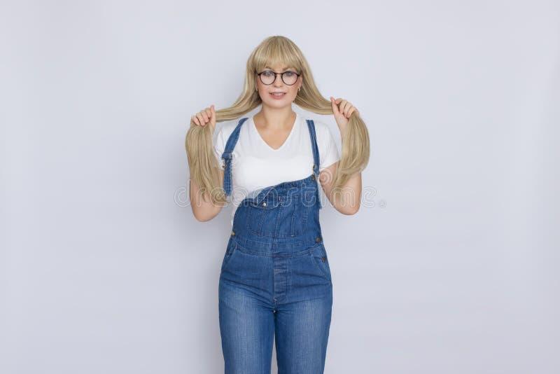Słodka piękna blond kobieta z długie włosy w niebieskich dżinsów szkłach nad popielatym tłem i kombinezonach zdjęcie royalty free
