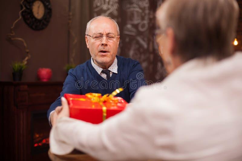 Słodka stara dama daje jej mężowi prezentowi podczas gdy ich za mieć gościa restauracji zdjęcie royalty free