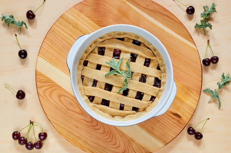 Słodki amerykański czereśniowy kulebiak w wypiekowym naczyniu na drewnianym tle dekorował z nowymi liśćmi i świeżymi wiśniami Jar obrazy royalty free