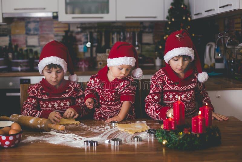 Słodki berbecia dziecko i jego stary brat, chłopiec, pomaga mamusi narządzania Bożenarodzeniowi ciastka w domu zdjęcie stock