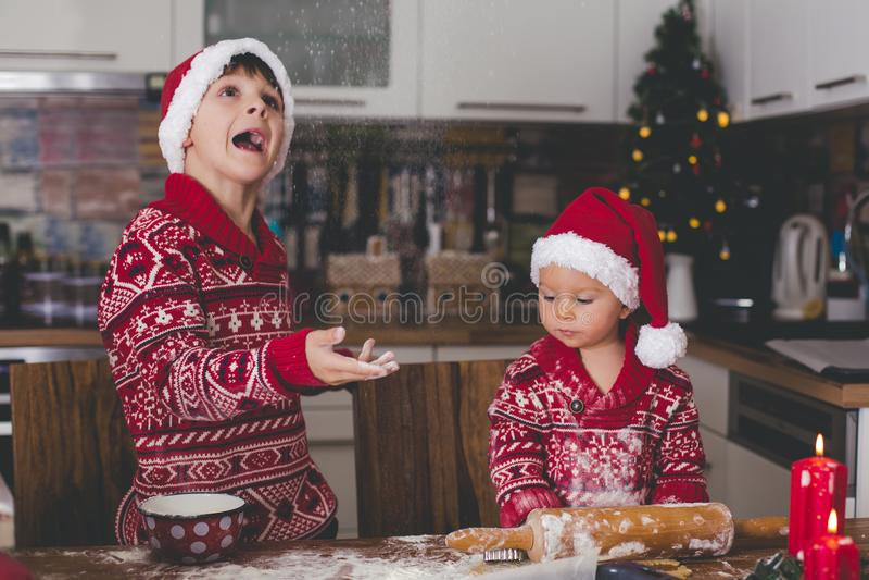 Słodki berbecia dziecko i jego stary brat, chłopiec, pomaga mamusi narządzania Bożenarodzeniowi ciastka w domu obrazy royalty free