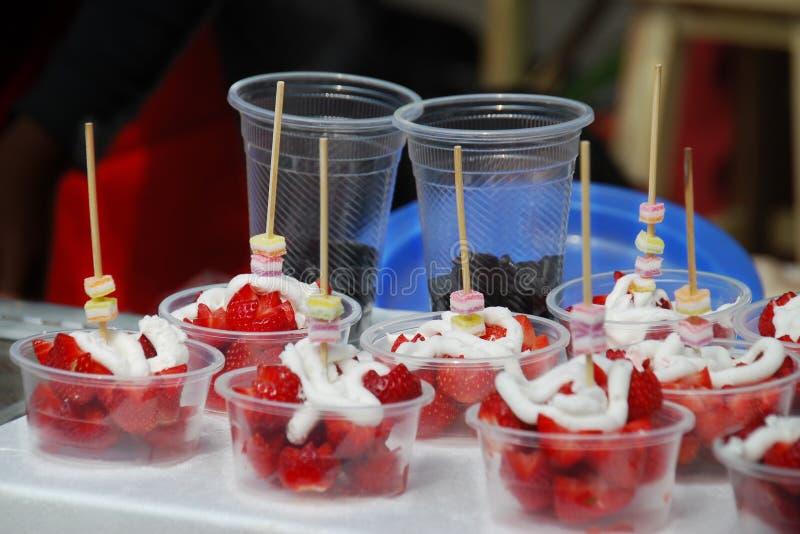 Słodki deser, Świeża truskawka i kolorowa galareta z batożącą kremową polewą, obrazy stock