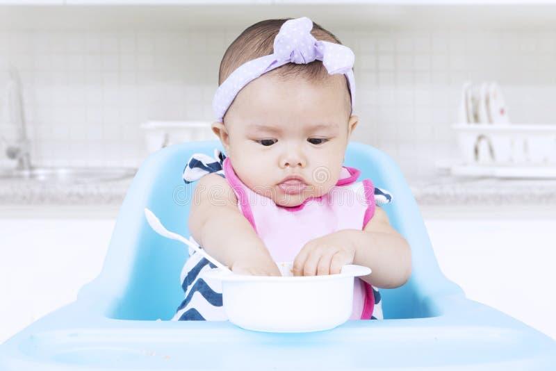 Słodki dziecka łasowanie z pucharem na krześle zdjęcia stock