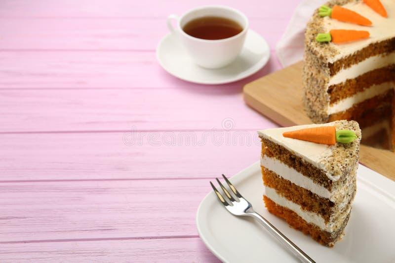 Słodki marchwiany tort z wyśmienicie śmietanką na różowym drewnianym stole zdjęcia royalty free