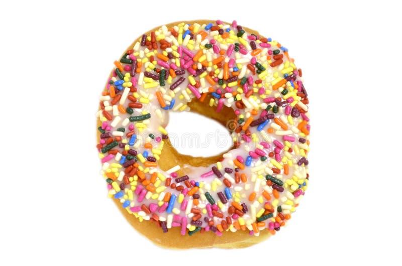Słodki pączek z tęcza cukierkiem kropi na odgórny odosobnionym na białym tle fotografia stock