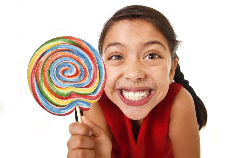 Słodki piękny łaciński żeński dziecko trzyma duże menchie ruszać się po spirali lizaka cukierek obrazy royalty free