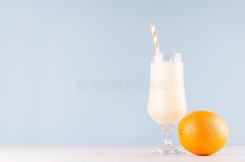 Słodki rozochocony milkshake w szkle z całymi pomarańczowymi i pasiastymi słoma na lekkim pastelowym błękitnym tle fotografia royalty free