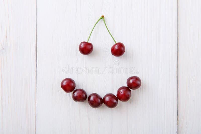Słodkie świeże wiśnie one uśmiechają się na białym drewnianym tle obrazy royalty free