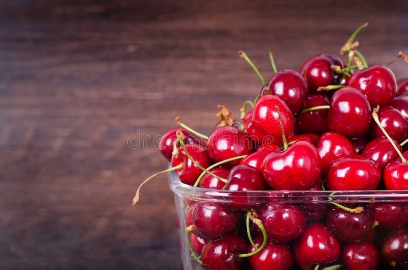 Słodkie czerwone wiśnie w szklanym pucharze na ciemnym drewnianym backgound z kopii przestrzenią Lato i żniwa pojęcie Weganin, ja obrazy stock