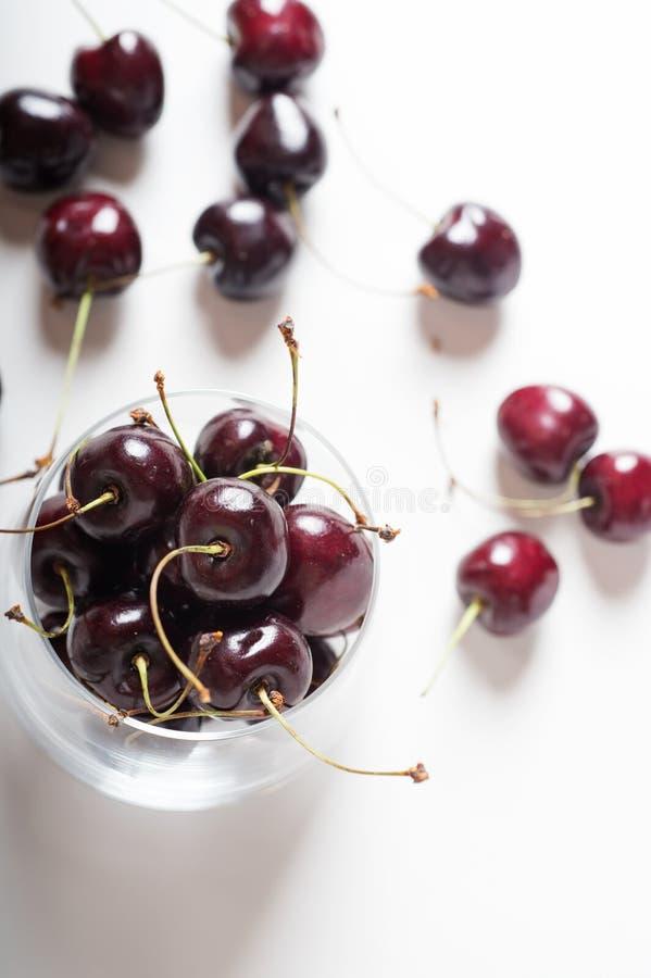 Słodkie wiśnie w czereśniowym szklanym pucharze wokoło bielu z bliska obraz royalty free