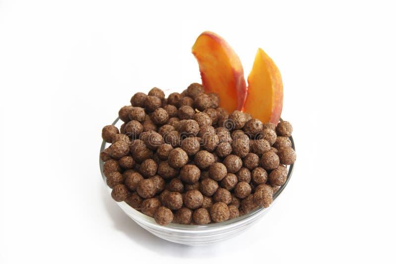 Słodkiej czekolady kukurydzane piłki w szklanym talerzu i brzoskwini na białym tle obraz stock