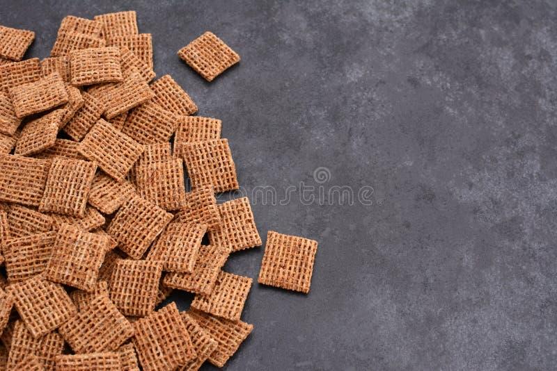 Słoduję strzępił pszenicznych ciastek śniadaniowego zboża na popielatych łupkowych półdupkach fotografia stock