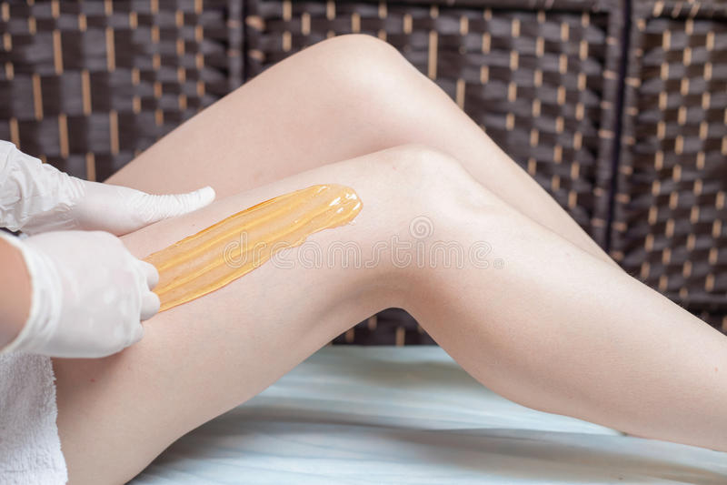 Słodzenie epilaci skóry opieka z ciekłym cukierem przy nogami fotografia royalty free