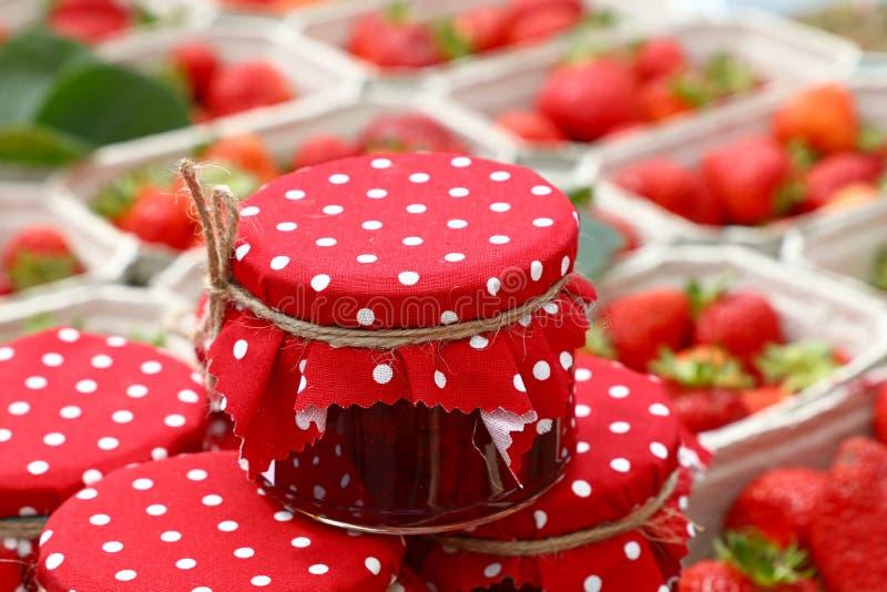 Słoje czerwony dżem nad świeżymi truskawkami fotografia stock