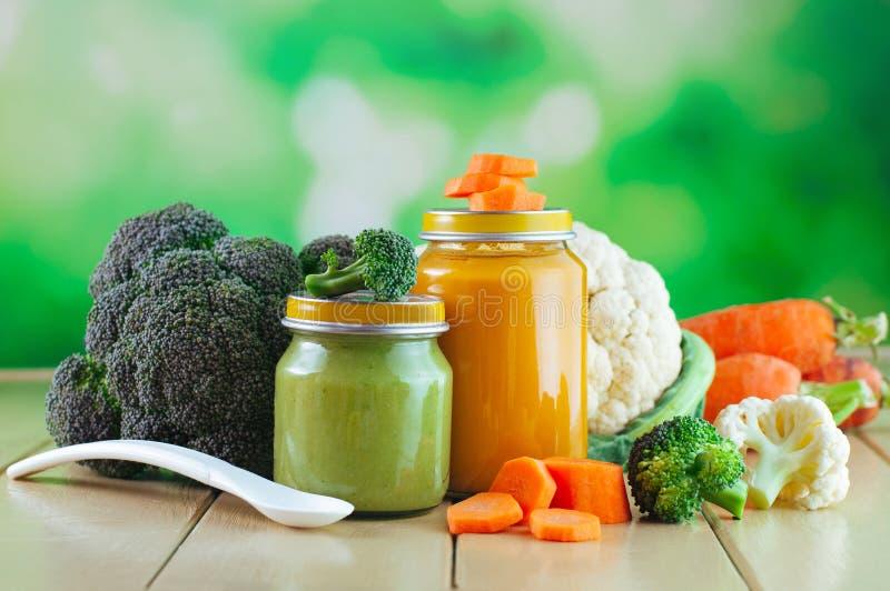 Słoje z jarzynowym puree blisko świeżych brokułów, kalafioru i marchewki, zdjęcia stock