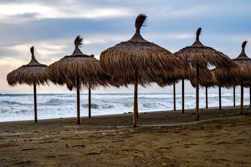 Słomiani parasole na brudnej plaży na burzowym dniu obrazy stock