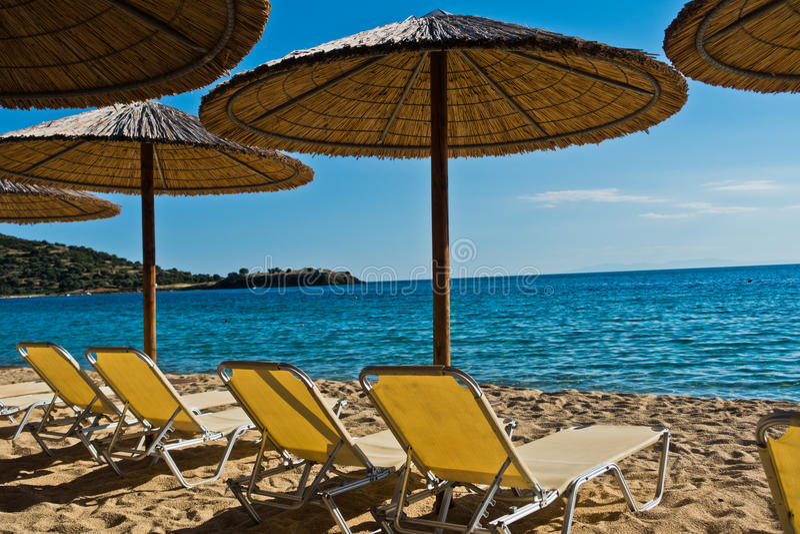 Słomiani parasols na plaży z ruinami stary rzymski forteca w tle, Sithonia fotografia royalty free