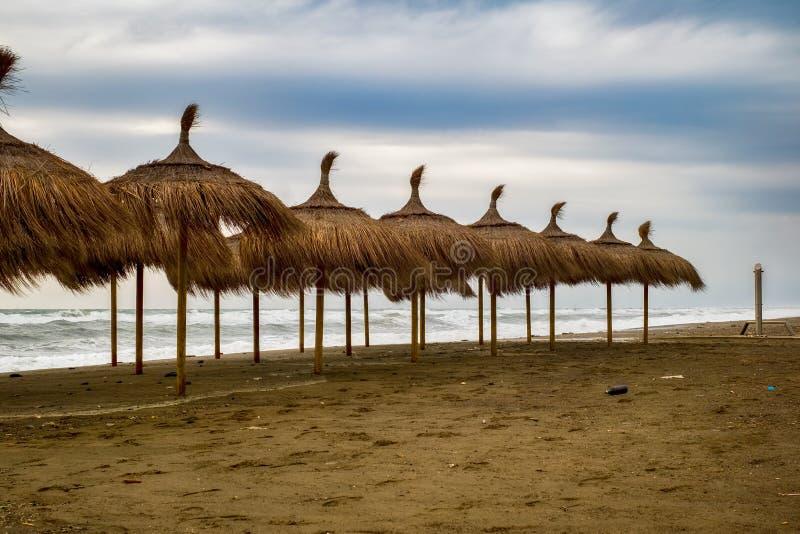 Słomiani plażowi parasole na plaży pełno śmieci obraz stock