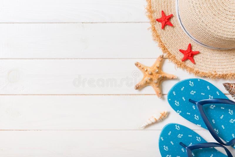Słomiany kapelusz, błękitne trzepnięcie klapy i rozgwiazda Na białym drewnianym tle, odg?rnego widoku wakacje letni poj?cie z kop zdjęcie royalty free