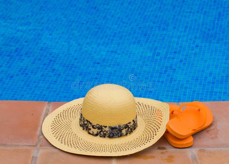 Słomiany kapelusz i sandały basen stroną zdjęcie stock