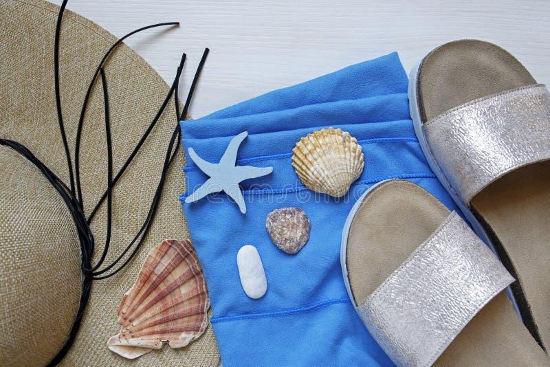 Słomiany kapelusz, kapcie, plażowy ręcznik i seashells, fotografia stock