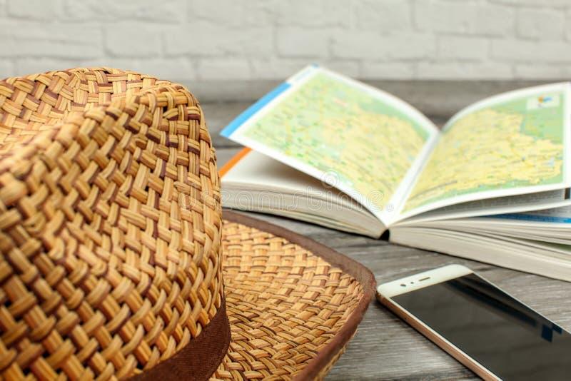Słomiany kapelusz, przewodnik z mapą i telefon komórkowy na szarym drewnie de, zdjęcia royalty free