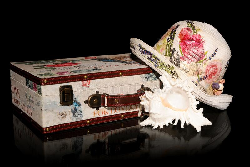 Słomiany kwiaciasty kapelusz, walizka i murex denna skorupa, obraz stock