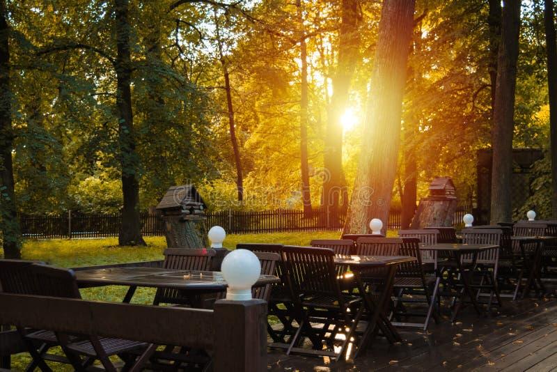 Słoneczny dzień w jesień parka restauraci z drewnianymi krzesłami i stołem zdjęcie stock