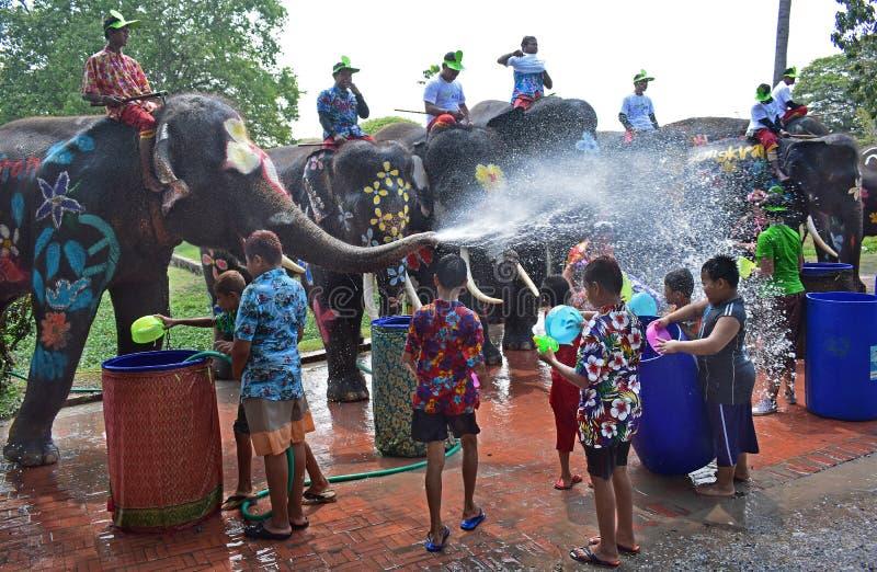 Słonie bawić się wodną bitwę z dziećmi podczas Songkran obrazy stock