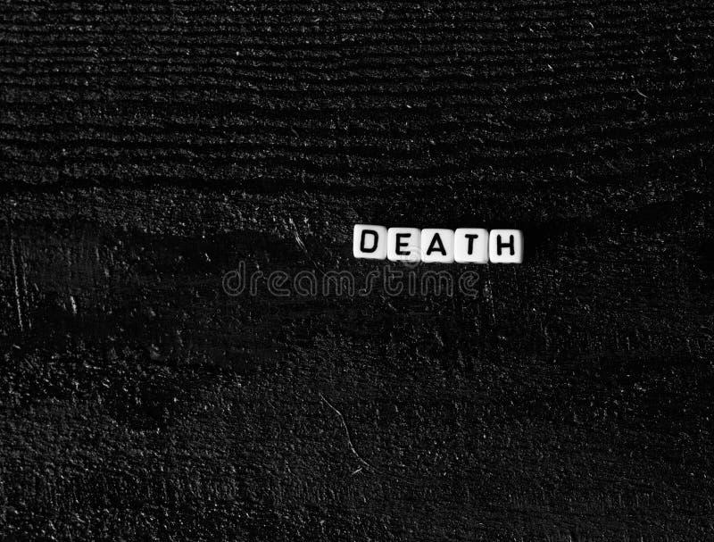 Słowa ` śmiertelny ` robić sześciany na czarnym drewnianym tle Czarny tło fotografia stock