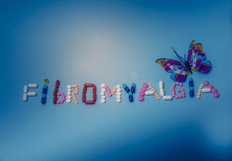 Słowa Fibromyalgia pisać kolorowymi medycynami, pigułki, leki, pastylki, kapsuły z purpurowym motylem na błękitnym tle zdjęcie stock