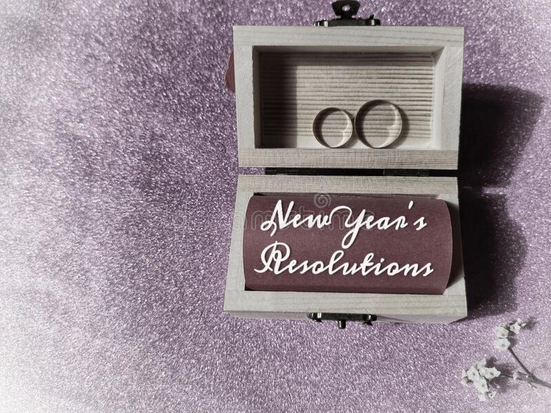 Słowa nowe rezolucje roku's napisane na papierze z małym drewnianym pudełkiem na skarb, pierścieniami i kwiatami w tle roczn obrazy royalty free