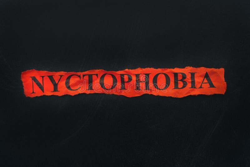 Słowa Nyctophobia na czerwień drzejącym kawałek papieru obraz stock