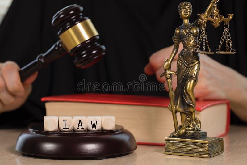 Słowa prawo komponujący drewniany dices Drewniany młoteczek i statua Themis w tle obrazy royalty free