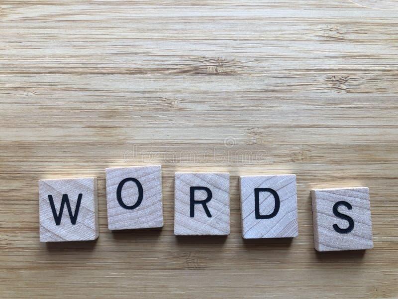 Słowa w drewnianych listach, odosobnionych na pomarańczowym tle zdjęcie stock
