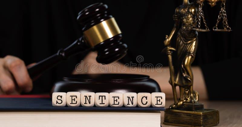 Słowa zdanie komponujący drewniany dices Drewniany młoteczek i statua Themis w tle zdjęcie stock