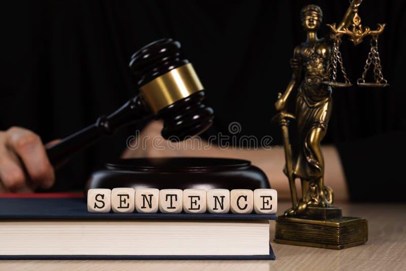 Słowa zdanie komponujący drewniany dices Drewniany młoteczek i statua Themis w tle fotografia royalty free