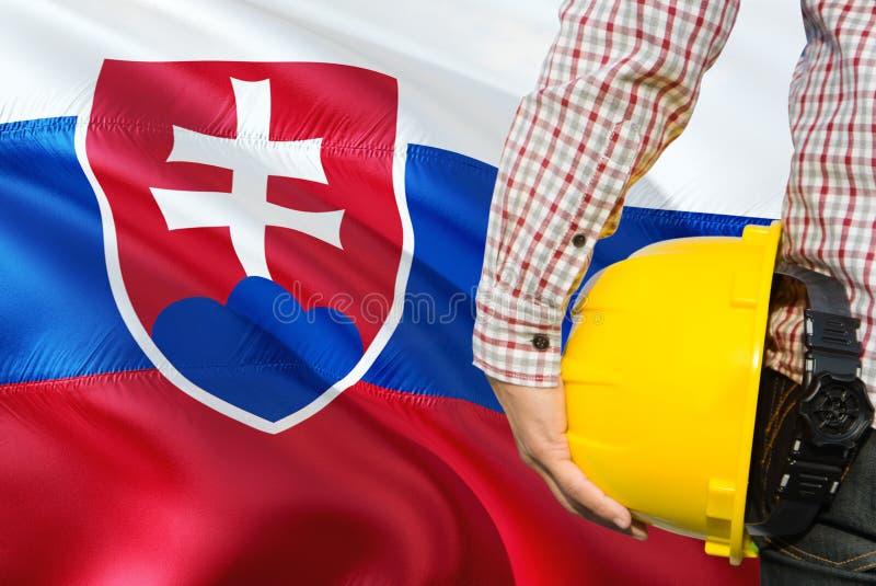 Słowacki inżynier trzyma żółtego zbawczego hełm z machać Sistani chorągwianego tło Budowy i budynku poj?cie obraz royalty free