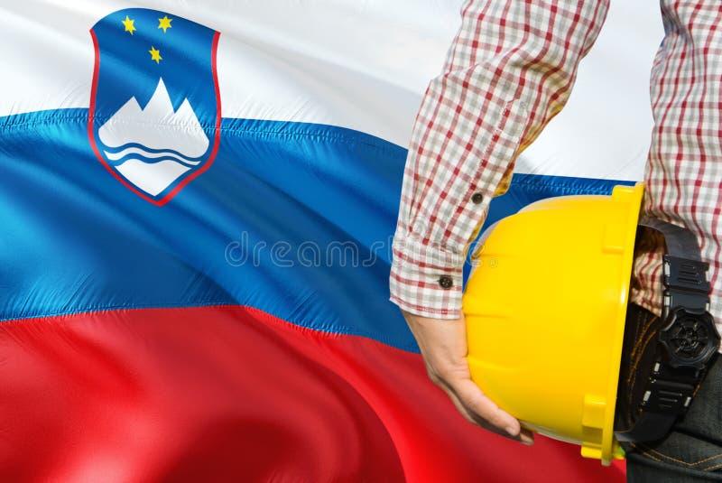 Słoweński inżynier trzyma żółtego zbawczego hełm z machać Slovenia chorągwianego tło Budowy i budynku poj?cie obraz royalty free