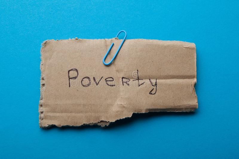 Słowo «ubóstwo «pisać na kartonie, odizolowywającym na błękitnym tle, pojęcie zdjęcie royalty free